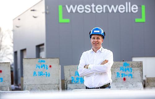 Geschäftsführer Kai-Uwe Westerwelle steht mit Helm vor dem Firmengebäude